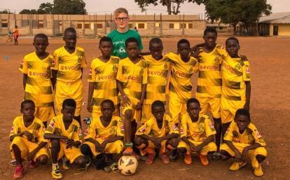 Een jonge vrijwilliger poseert met zijn leerlingen tijdens zijn sport vrijwilligersproject in Ghana.